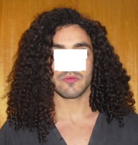 A male with long curly hair that is growing